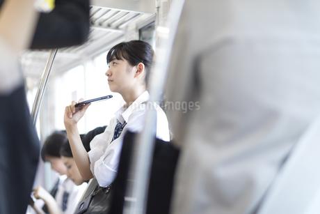電車でスマホを持ち遠くを見つめる女子高校生の写真素材 [FYI02973477]