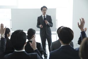 マイクを手に講義をするビジネス男性の写真素材 [FYI02973481]