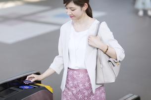 改札で定期券をかざすビジネス女性の写真素材 [FYI02973482]
