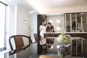 キッチンでパソコンを見る夫婦の写真素材 [FYI02973497]