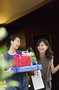 花束やプレゼントボックスを持って店を出る女性2人の写真素材 [FYI02973500]