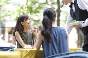 オープンカフェで食事をする女性2人の写真素材 [FYI02973508]