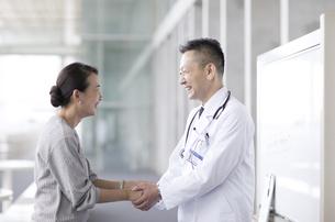 手を握り感謝をする患者と男性医師の写真素材 [FYI02973513]