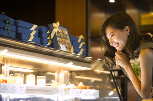 ショーウィンドウのケーキを選ぶ女性の写真素材 [FYI02973514]