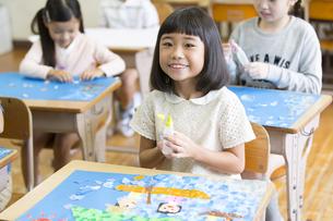 教室で貼り絵を楽しむ女の子の写真素材 [FYI02973517]