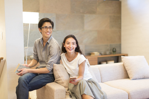 ソファーに座り遠くを見る夫婦の写真素材 [FYI02973526]
