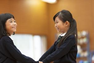 体育館で手を繋いで微笑む小学生の女の子2人の写真素材 [FYI02973527]