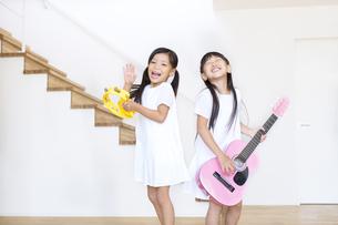 タンバリンを叩く女の子とギターを弾く女の子の写真素材 [FYI02973531]