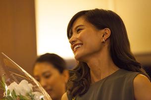 花束を持って笑う女性の横顔の写真素材 [FYI02973541]
