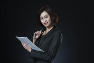 資料とペンを手に持つビジネス女性の写真素材 [FYI02973546]