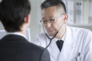 患者に聴診器をあてる男性医師の写真素材 [FYI02973551]