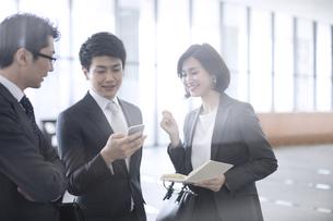 スマートフォンを見て打ち合わせをする3人のビジネス男女の写真素材 [FYI02973554]