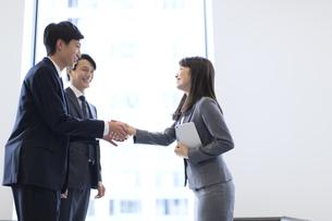 オフィスビルのロビーで握手をするビジネス男女の写真素材 [FYI02973555]