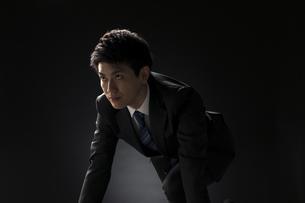駆け出すポーズをとるビジネス男性の写真素材 [FYI02973560]