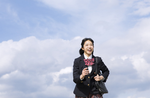 青空をバックに走る女子高校生の写真素材 [FYI02973567]