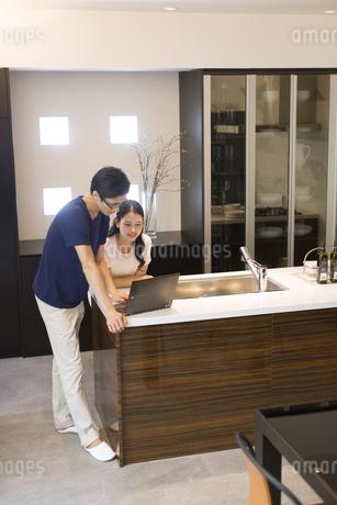 キッチンでパソコンを見る夫婦の写真素材 [FYI02973568]