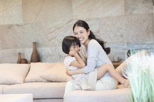 ソファーで戯れる母親と娘の写真素材 [FYI02973580]