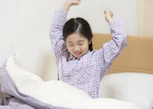 ベッドで背伸びをする女の子の写真素材 [FYI02973581]