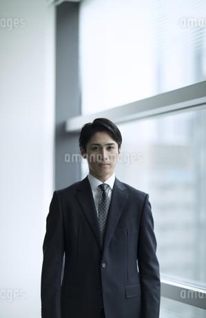 窓の横でカメラ目線で立つビジネス男性の写真素材 [FYI02973592]