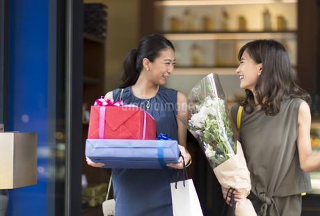 花束やプレゼントボックスを持って店を出る女性2人の写真素材 [FYI02973593]