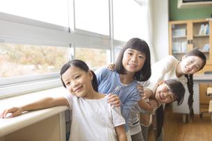 教室の窓際で重なって笑う女の子たちの写真素材 [FYI02973599]