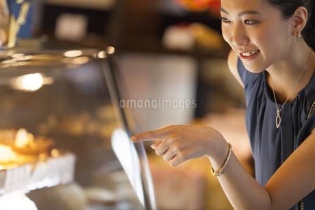 ショーウィンドウのケーキを選ぶ女性の写真素材 [FYI02973603]