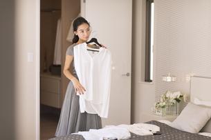 洋服を合わせる女性の写真素材 [FYI02973605]