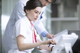 男性医師と打ち合わせをする女性看護師の写真素材 [FYI02973609]