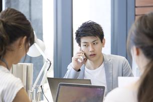 PCを見て電話をするビジネス男性の写真素材 [FYI02973611]