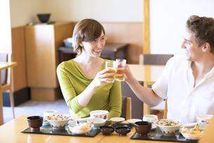日本料理を注文し乾杯する外国人の男女の写真素材 [FYI02973612]