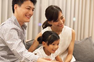ソファーに座ってテレビを見て笑う家族の写真素材 [FYI02973614]