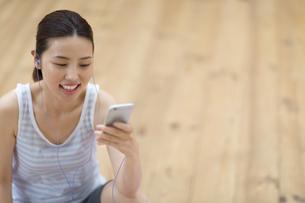 スマートフォンで音楽を楽しむ女性の写真素材 [FYI02973618]