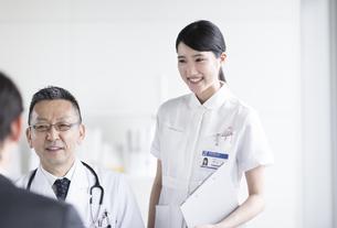 患者に問診をする医師の横で対応する女性看護師の写真素材 [FYI02973619]