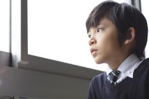 教室の窓際で外を眺める小学生の男の子の写真素材 [FYI02973620]