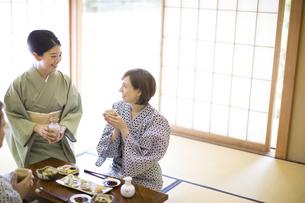 料理を前に女将と話しをする外国人観光客の写真素材 [FYI02973636]