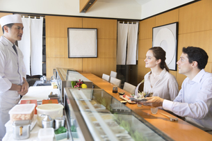 寿司職人と話しをする外国人の男女の写真素材 [FYI02973637]