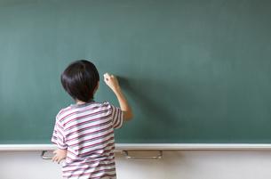 黒板に文字を書こうとする男の子の写真素材 [FYI02973643]