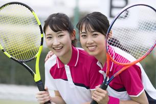 テニスラケットを持ちカメラ目線の女子学生たちの写真素材 [FYI02973648]