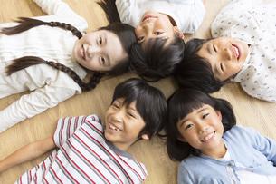 床に寝転んで笑う子供たちの写真素材 [FYI02973649]