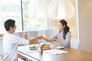 ダイニングテーブルで食事を楽しむ夫婦の写真素材 [FYI02973655]