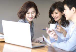 ノートパソコンを見る3人のビジネス男女の写真素材 [FYI02973656]