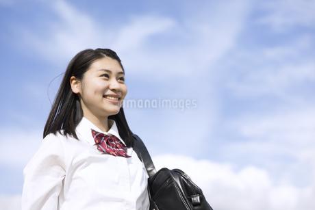 青空をバックに立つ女子高校生の写真素材 [FYI02973659]