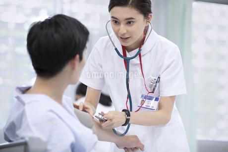 血圧を測る女性看護師の写真素材 [FYI02973660]