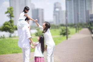 肩車して遊歩道を歩く家族の後ろ姿の写真素材 [FYI02973665]