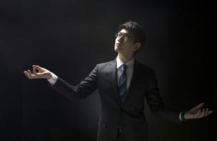 両手を広げ上を見上げるビジネス男性の写真素材 [FYI02973671]