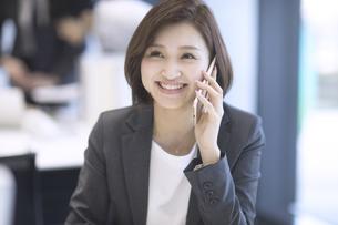 スマートフォンで通話するビジネス女性の写真素材 [FYI02973678]