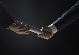 バトンを渡すビジネス男性の手元の写真素材 [FYI02973683]