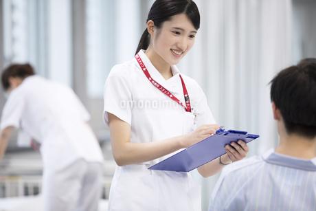 入院患者と会話をする女性看護師の写真素材 [FYI02973686]