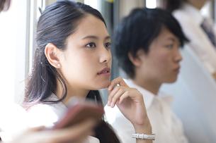 電車の座席に座り遠くを見つめるビジネス女性の写真素材 [FYI02973688]