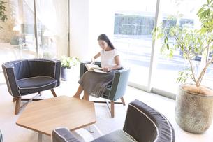 椅子に座り本を読む女性の写真素材 [FYI02973693]